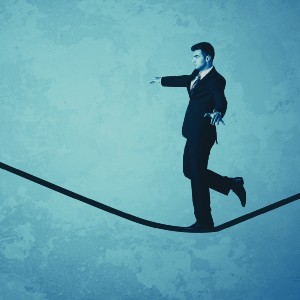 photo of man in business suit walking on tightrope
